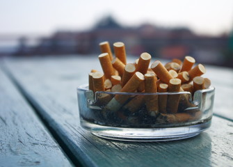 Ashtray full of cigarettes butts outdoor on green wooden table