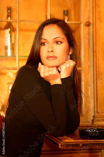 Bella donna in un locale con i pugni chiusi sul mento guarda assorta verso fuori in un - Un locale con tavola calda ...