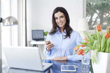 Send a message. Portrait of an attractive young businesswoman using her cellphone and text messaging while working in the office.