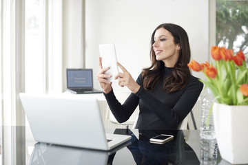 Capture the moment. Shot of a young businesswoman sitting in front of laptop and taking selfie with her mobile phone while working from home.