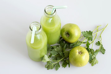 Source of natural vitamins. Glass bottles with fresh juice, green apples and sprigs of parsley on a light background.