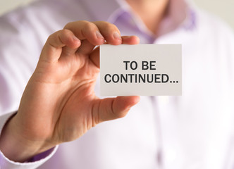 Businessman holding a card with TO BE CONTINUED message