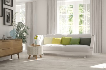 White room with sofa and green landscape in window. Scandinavian interior design