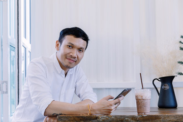 Asian man using a mobile phone and drink coffee in  bakery shop