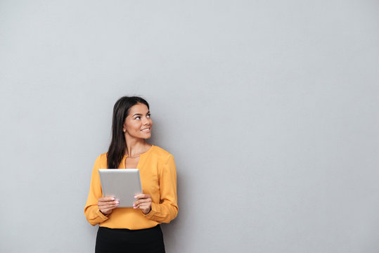 Business woman holding tablet computer and looking away