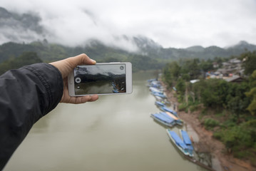 Closeup of a hand. Take a photo boat,river and mountains with mobile phone.