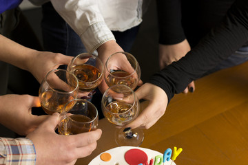 People drink at the table, clink glasses. Cheers!