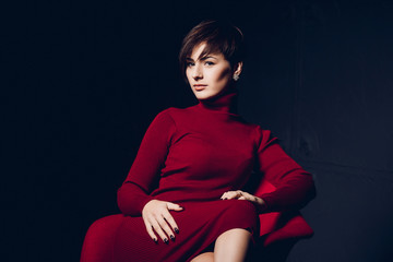 Attractive woman in red. Fashion portrait of a sexy young business lady in a red dress on a dark background