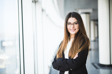 Businesswoman crossed hands portrait in office with panormic windows.