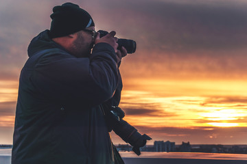 Photographer with two cameras taking a shot of sunset from roof