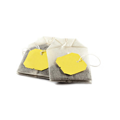Two (2) Isolated tea bags on a pure white background with yellow tags.