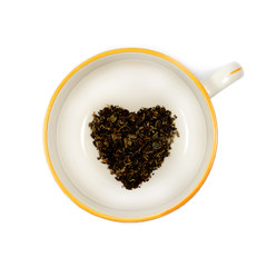 Heart shaped organic black tea in a large white mug isolated on a pure white background.