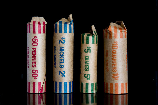 Coin rolls on black back round.