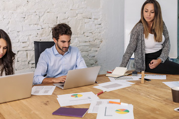 Young businesswoman and businessman during a meeting in office to launch start-up. They speak, work laptop, show graphs, charts