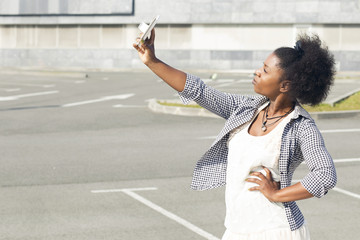 African woman taking selfie on her smartphone, posing, looking at it. Outdoors, walking on the street near a empty parking lot.