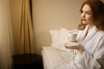 Red-haired girl in a white robe with a cup of coffee sitting on a bed