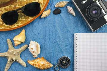 Top view, sea and travel concept with summer holiday accessories, vintage camera, sunglasses, seashells.