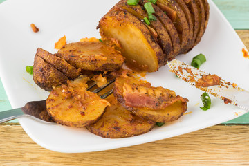 Hasselback potato with smoked paprika and bacon.
