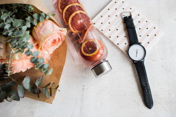 Feminine tabletop, flowers, water with fruits and watch