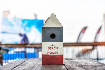 Beach House or Nest House with summer background on wooden table, closeup