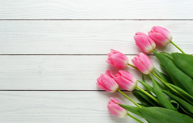 a bouquet of pink tulips on a white wooden background