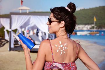 beautiful woman with suntan lotion sunscreen solar cream on the beach