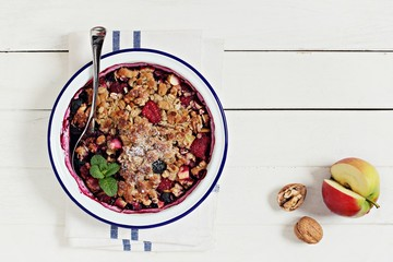 Apple-berry crumble with oatmeal and nuts crunch. Clean eating concept.Rustic style.