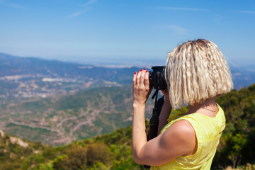 Female traveler enjoying the views from the mountains of Montserrat in Spain and makes a photo on her camera. The girl in a yellow dress on background of the nature