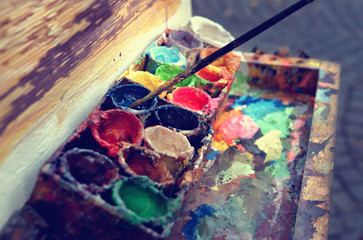 Artist at work. The workplace of the artist, brushes, paints and canvas. Multicolor oil paints on a palette close up.
