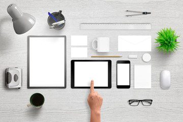 Office supplies with smart phone and tablet with isolated white screen for mockup. Corporate brand design presentation. Top view of white wooden desk.
