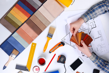 Decorator holding a color swatches. Painting tools all around on table
