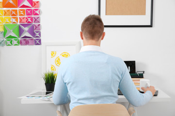 Back view of young man at workplace