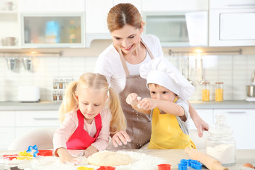 Young mother with kids making biscuits on table