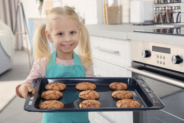Little girl holding biscuits on tray