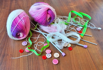Skeins of thread, buttons, needles  and measuring tape on wooden background.