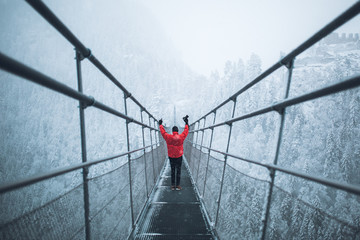 man with red jacket on bridge