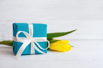 Packaged gift and yellow tulip. Concept of holiday, birthday, Easter, March 8.