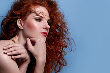 Beautiful red-haired cute girl with curly hair, in profile view, looking thoughtful. The girl with a gentle makeup on her face. Freckles on the face of the girl.