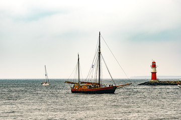 Sailing ship on the sea. Tall Ship and lighthouse Yachting travel.