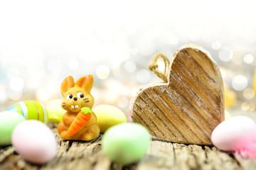 Kleiner Marzipan Osterhase auf altem Holzuntergrund mit Ostereiern und Herz