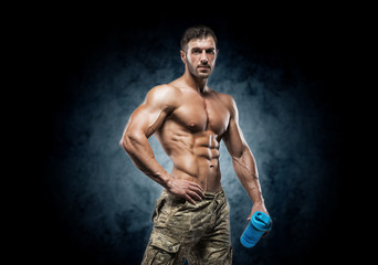 Muscular young man in studio on dark background