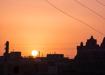 sunset over Ghoortan citadel by village near Varzaneh in Iran