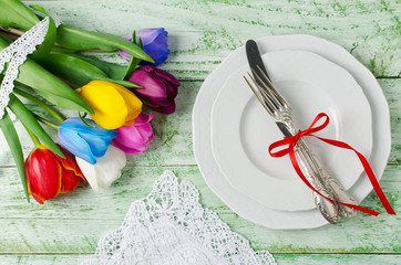 Multicolored tulips on a shabby green table