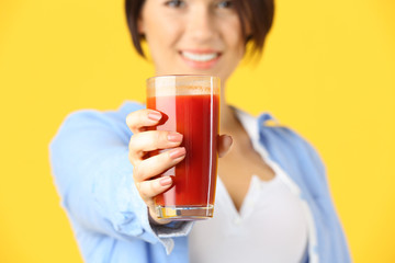 Young beautiful woman with glass of tomato juice, on yellow background