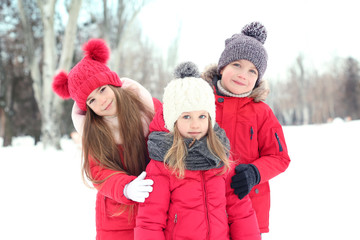 Happy children in red warm clothing having fun outdoors in winter