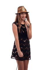 Young girl with long hair wearing a black dress and gold hat with a microphone on a white background in studio