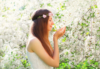 Beautiful woman enjoying smell spring flowers over flowering garden background