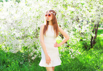 Fashion beautiful woman over flowering garden background on grass