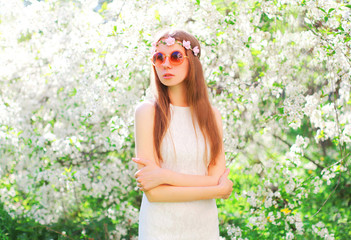 Fashion beautiful young woman over flowering garden background