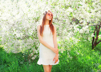 Fashion beautiful young woman over flowering garden background on grass
